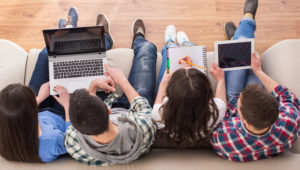 College students sitting while using their laptops