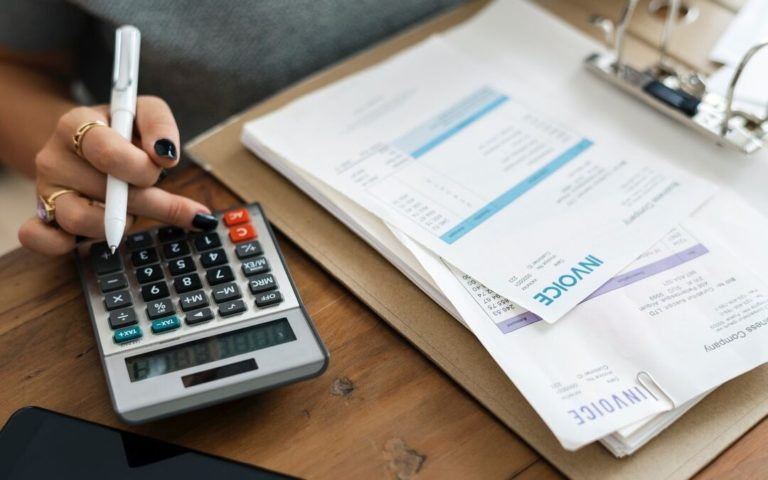 An accountant with Tax Invoice documents and a calculator on the desk