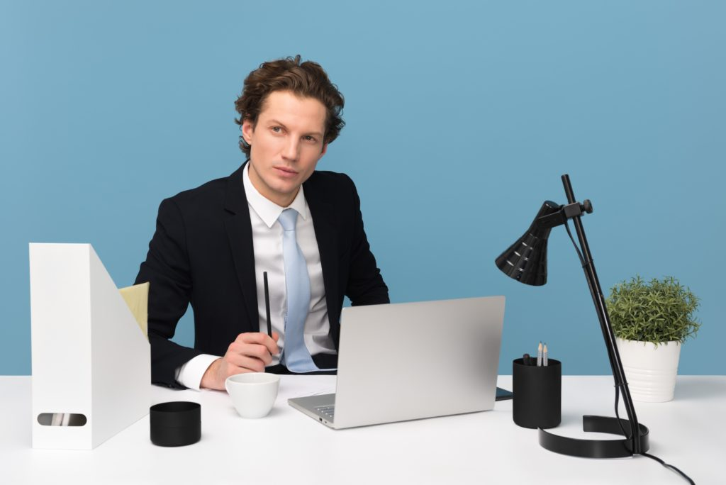 a business manager sitting on a chair besides a laptop
