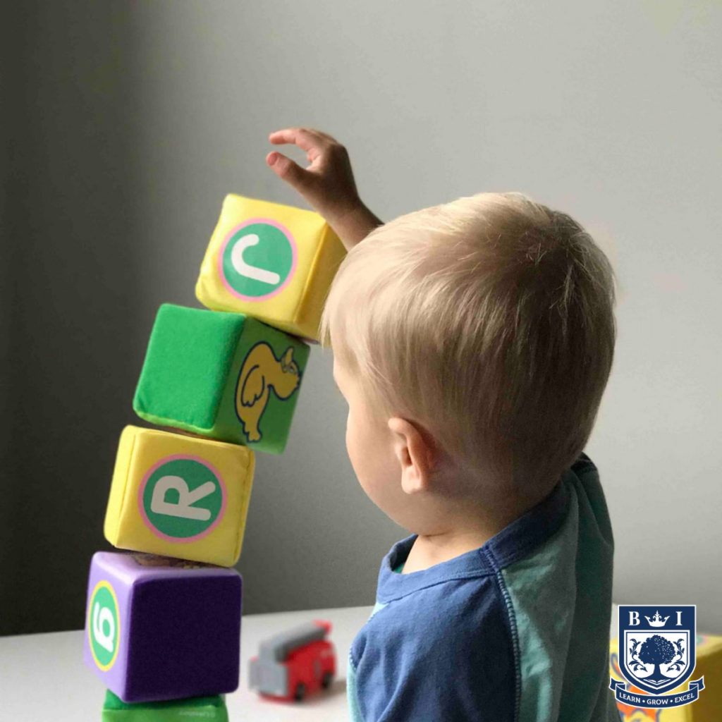 A picture of a child learning by building blocks - educare, with the bellview logo