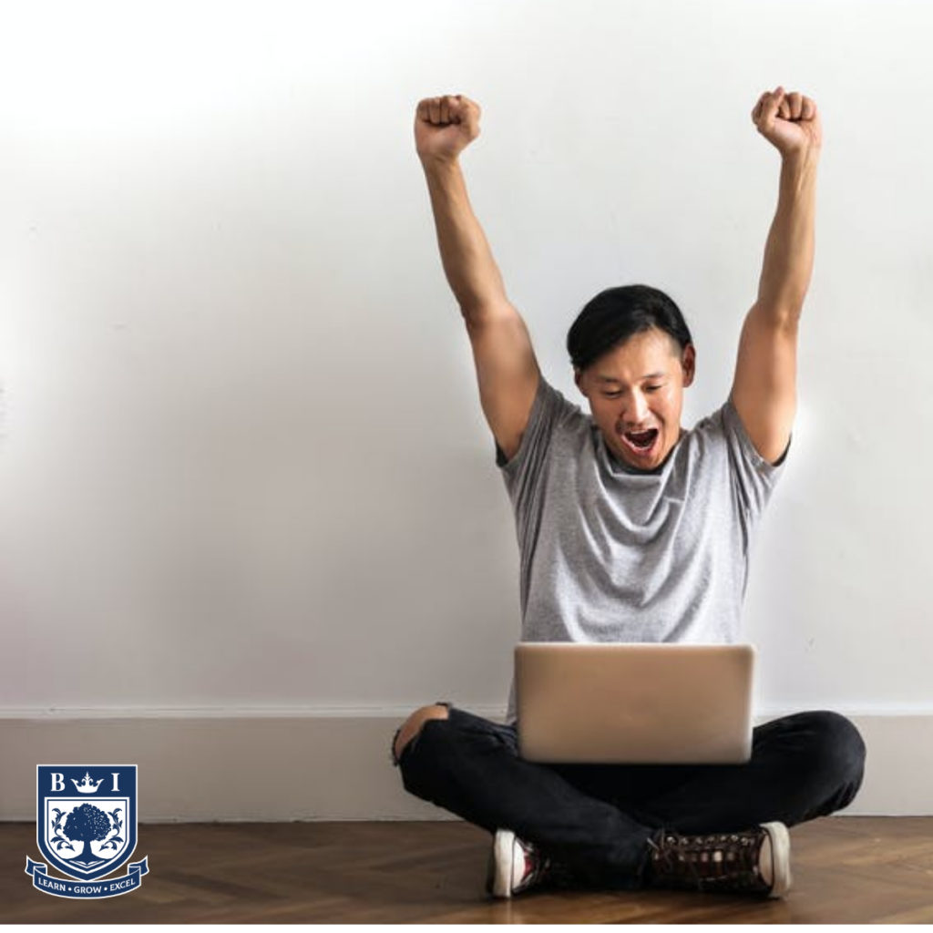 Picture of a man sitting with his laptop on the floor celebrating landing his dream job. With the Bellview logo in the corner