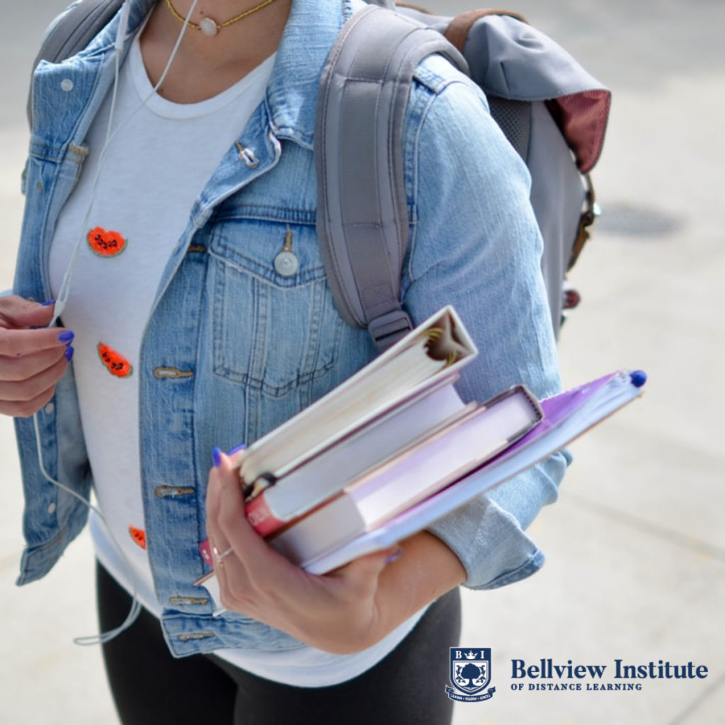 Woman holding academic books, with Bellview logo in the corner.