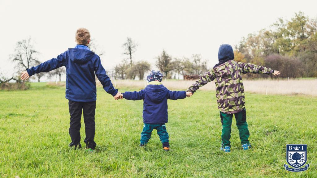 Three children holding hands in a field. Bellview logo in the corner.