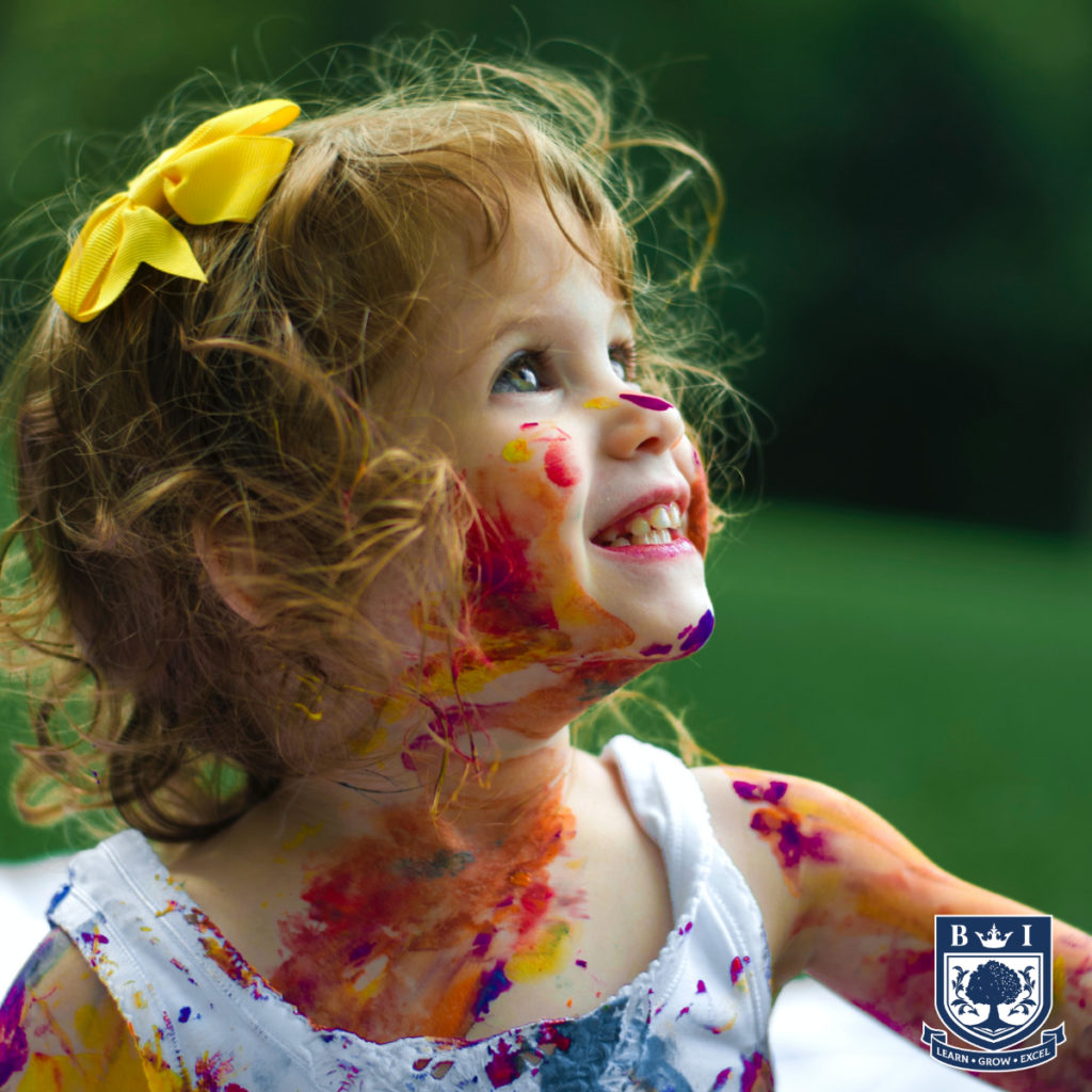 Child with paint on her face. Bellview logo in the corner.